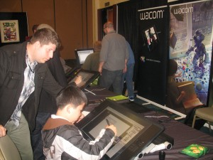 Perry Chen drawing on Wacom Cintiq tablet as Kevin Sean Michaels watches (photo by Zhu Shen)