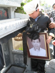 Perry Chen holding Changyou's photo at the burial (photo by Zhu Shen)
