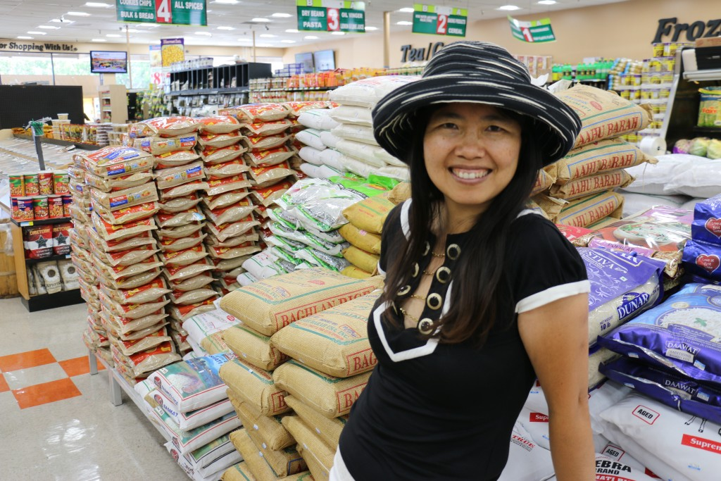 Zhu Shen surrounded by bulk rice at Harvest International Market (photo by Perry Chen)